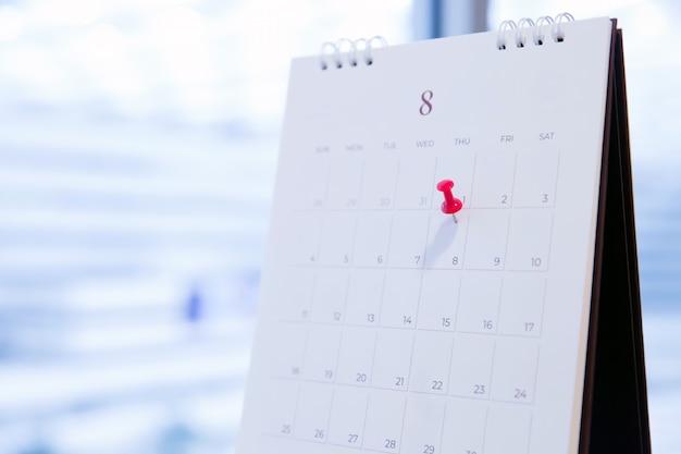 Pin rosso sul calendario per la pianificazione aziendale e la riunione. Foto Premium