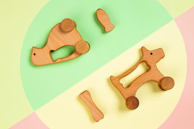 Pinguino di giocattoli di legno con pesce, cane con un osso su sfondo isolato rosa, verde e giallo. Foto Premium