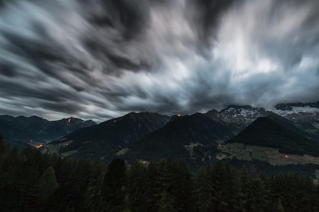 Pini di lasso di tempo vicino alle montagne sotto grey clouds Foto Gratuite