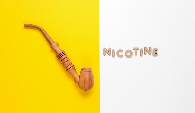 Pipa in legno con la parola nicotina di lettere in legno Foto Premium