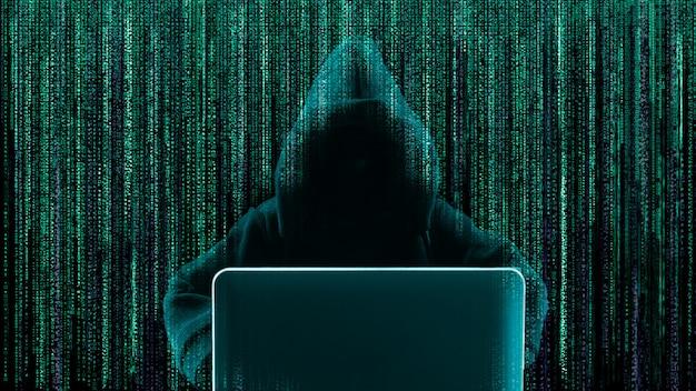 Pirata informatico che per mezzo del computer portatile con il codice binario di forma astratta del cranio. Foto Premium