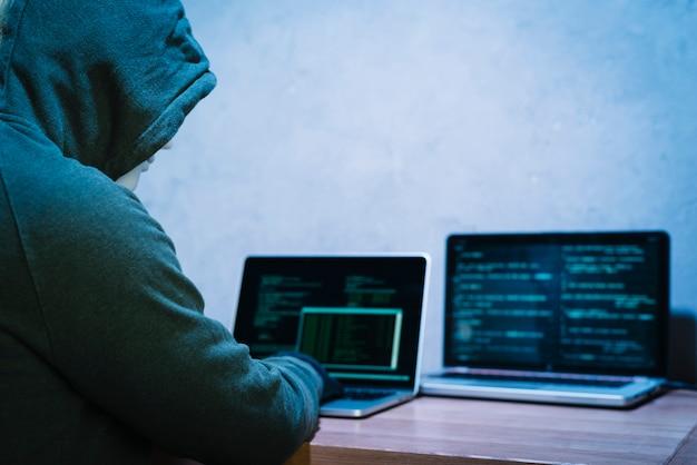 Pirata informatico che scrive sul computer portatile Foto Gratuite