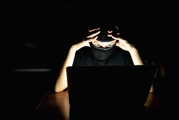 Pirata informatico di computer che fa il suo lavoro con il computer portatile nella stanza scura Foto Gratuite