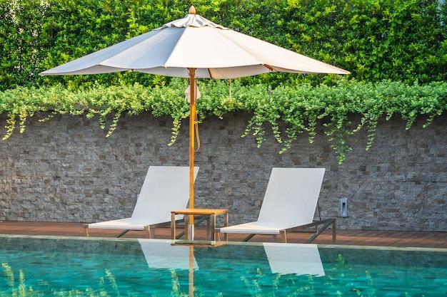 Piscina all'aperto con ombrellone salotto qui per i viaggi di piacere Foto Gratuite