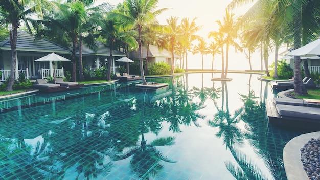 Piscina di lusso di fronte a ville tropicali private in hotel Foto Premium