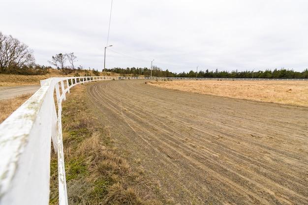Pista da corsa vuota per cavalli da corsa, pista di sabbia e recinzione bianca Foto Premium