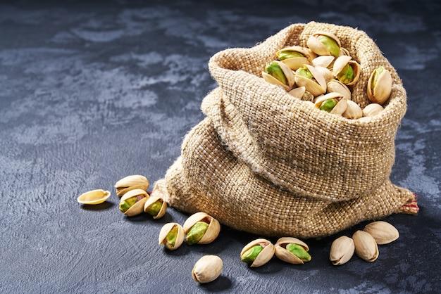 Pistacchi in borsa sulla tavola nera. mucchio o pila di pistacchi. Foto Premium