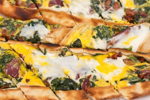 Pita di tortilla turca con pancetta pastorizia, uova ed erbe verdi. Foto Premium