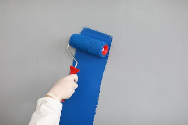 Pittore maschio in uniforme dipinge la parete con il rullo Foto Premium