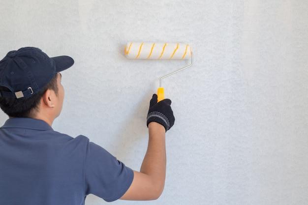 Pittore uomo al lavoro con un rullo di vernice sul muro Foto Premium