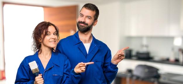 Pittori che indicano il lato con un dito per presentare un prodotto in casa Foto Premium