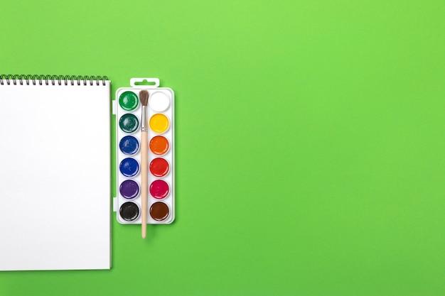 Pitture e spazzole dell'acquerello con tela per la pittura con copyspace su fondo verde Foto Premium