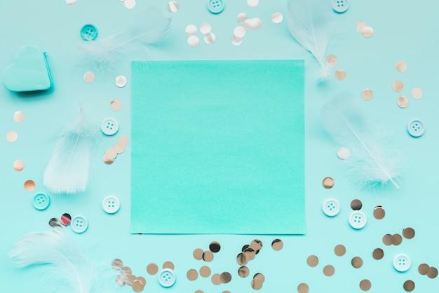 Piuma; paillettes; pulsanti circondati intorno alla carta turchese sullo sfondo verde acqua Foto Gratuite