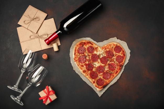 Pizza a forma di cuore con mozzarella, salsiccia, bottiglia di vino, due bicchiere da vino, confezione regalo su sfondo arrugginito Foto Premium