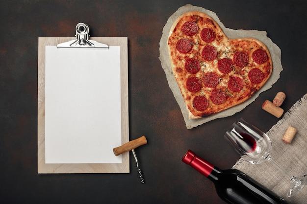 Pizza a forma di cuore con mozzarella, salsiccia, bottiglia di vino e tablet Foto Premium