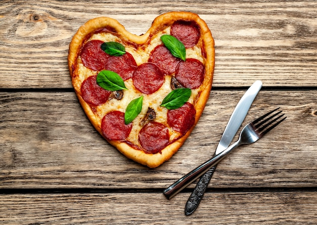Pizza a forma di cuore su un tavolo di legno Foto Premium