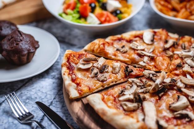Pizza ai funghi vista laterale con salsa di pomodoro formaggio pepe pepe e champignon su una tavola Foto Gratuite
