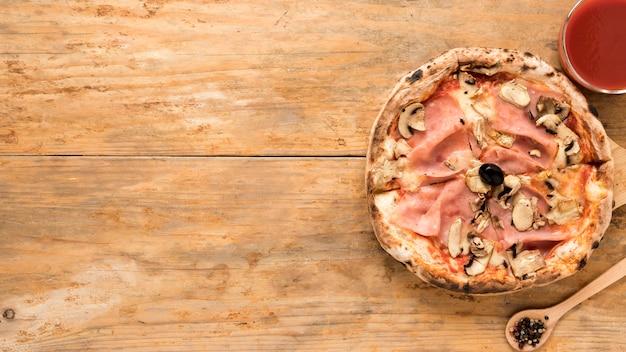 Pizza al forno funghi e pancetta con salsa di pomodoro sul vecchio tavolo di legno Foto Gratuite