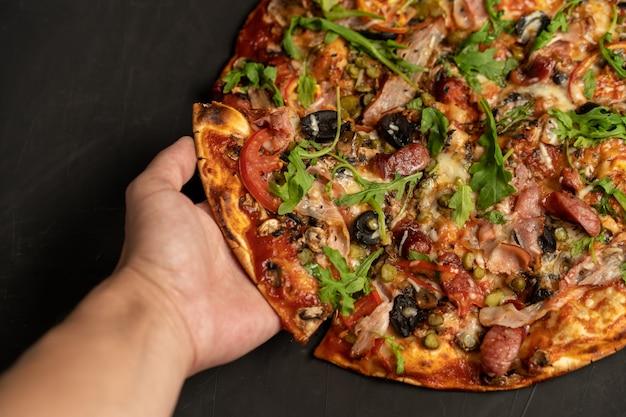 Pizza appetitosa con la rucola affumicata del formaggio del pomodoro della carne della pancetta affumicata delle salsiccie su oscurità nera. con copyspace Foto Premium