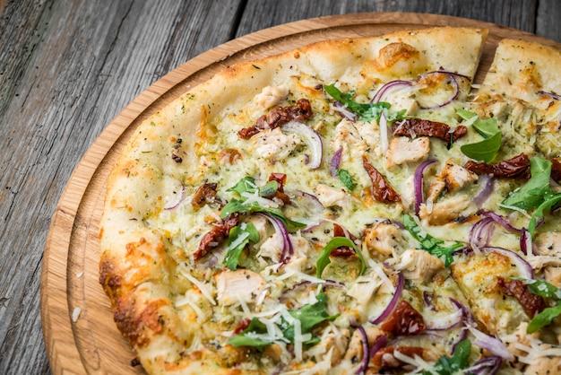 Pizza con pomodori secchi, prosciutto, rucola e parmigiano Foto Premium
