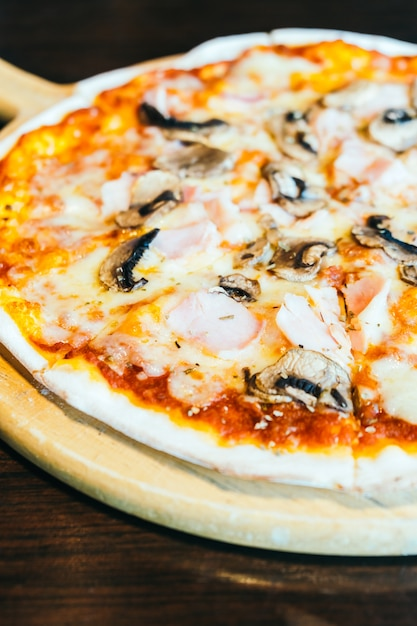 Pizza con prosciutto e funghi Foto Gratuite