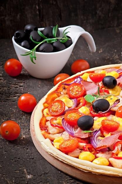 Pizza con verdure, pollo, prosciutto e olive isolati su bianco Foto Gratuite