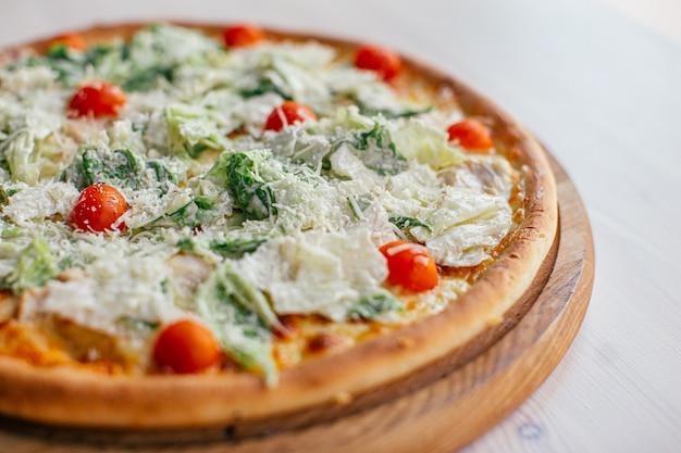 Pizza deliziosa fresca con lattuga e i pomodori ciliegia Foto Premium