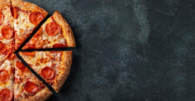 Pizza di peperoni saporita su uno sfondo di cemento nero. Foto Premium