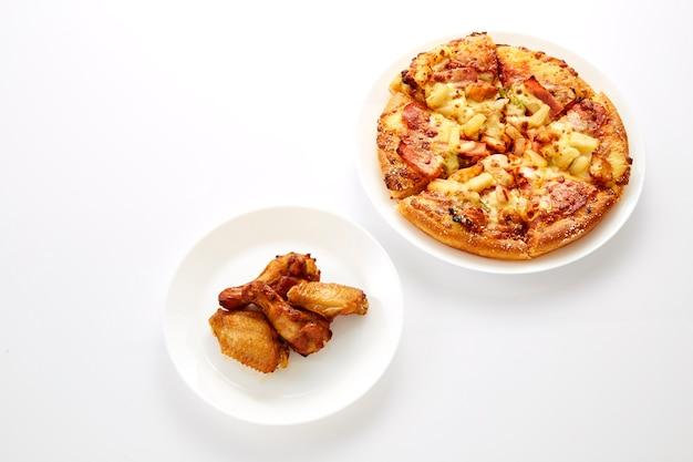 Pizza e polli fritti sono piatti bianchi Foto Premium