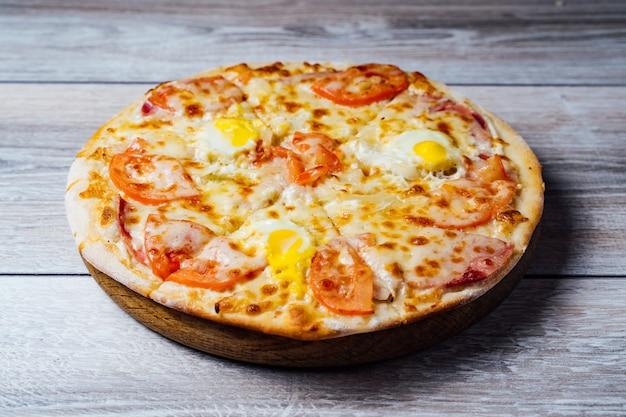 Pizza fresca su supporto in legno sul tavolo. Foto Premium