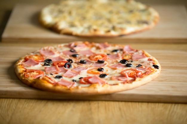 Pizza italiana su tavole di legno sul tavolo del ristorante, concetto di pizzeria Foto Gratuite
