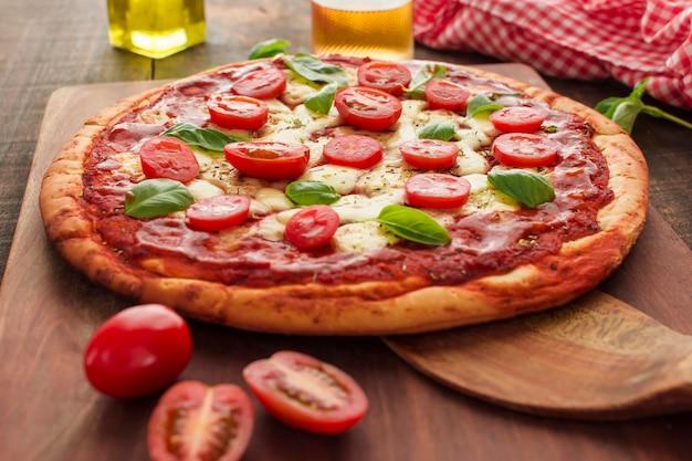 Pizza margherita fatta in casa sul tagliere di legno Foto Gratuite