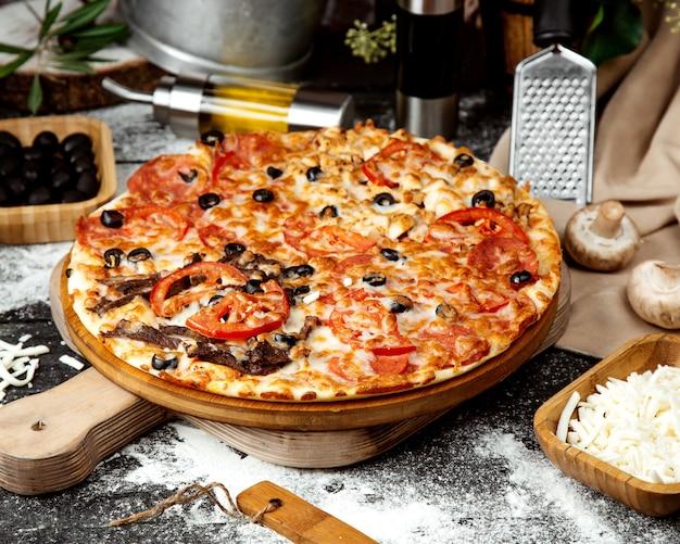 Pizza mista con carne di pollo e salame piccante Foto Gratuite