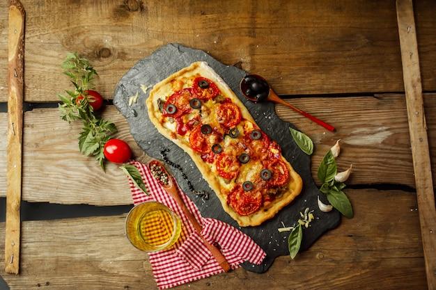 Pizza mista con pollo, pepe, olive, cipolla, basilico su tagliere Foto Premium