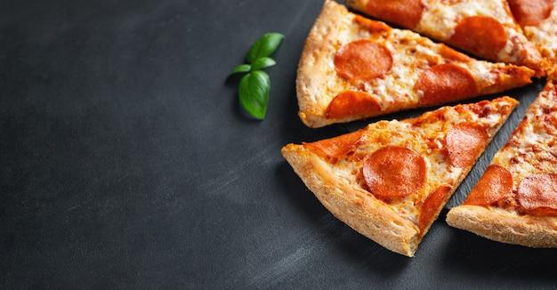 Pizza peperoni saporita su fondo concreto nero Foto Premium