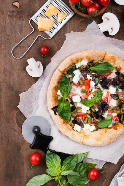 Pizza piana di disposizione su fondo di legno Foto Gratuite