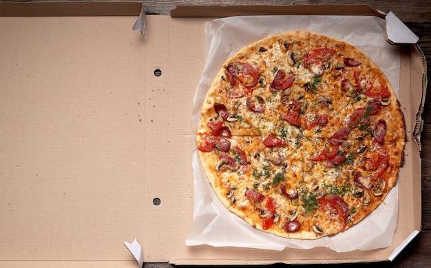 Pizza tonda al forno con salsicce affumicate, funghi, pomodori, formaggio e aneto in una scatola di cartone aperta Foto Premium