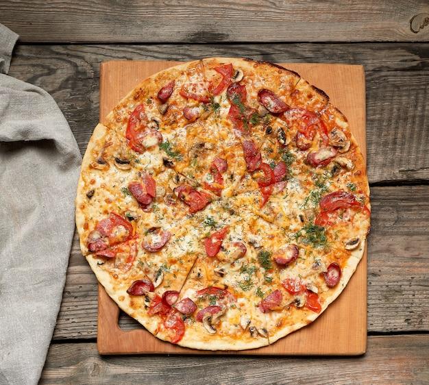 Pizza tonda al forno con salsicce affumicate, funghi, pomodori, formaggio Foto Premium