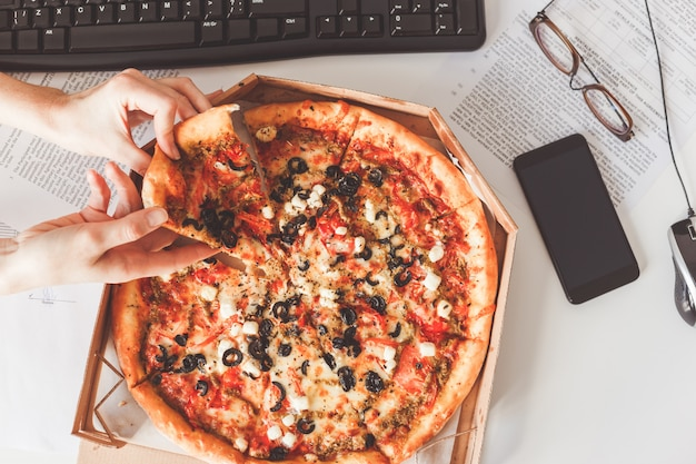 Pizza vegetariana sul tavolo dell'ufficio Foto Premium
