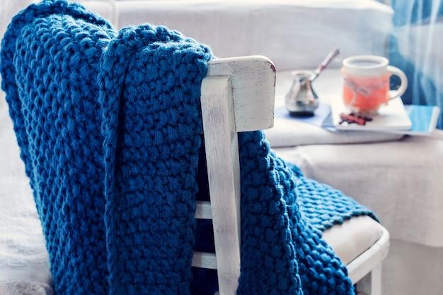 Plaid blu su una sedia e caffè con cezve Foto Premium