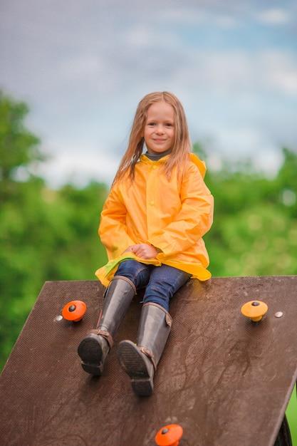 Playng felice della bambina sul campo da giuoco all'aperto Foto Premium