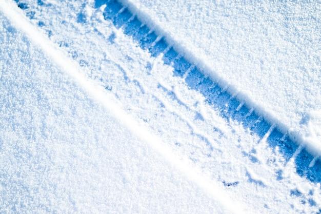 Pneumatici per auto sulla strada invernale. priorità bassa di inverno di natale con neve Foto Premium