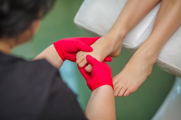 Podologo che tratta il fungo dell'unghia del piede. trattamento podologico Foto Premium