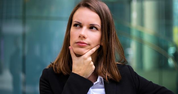 Poirtrait sorridente della donna di affari in un'espressione pensierosa Foto Premium