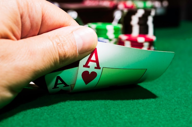 Poker chips e asso di picche e asso di cuori su un tappeto verde Foto Premium
