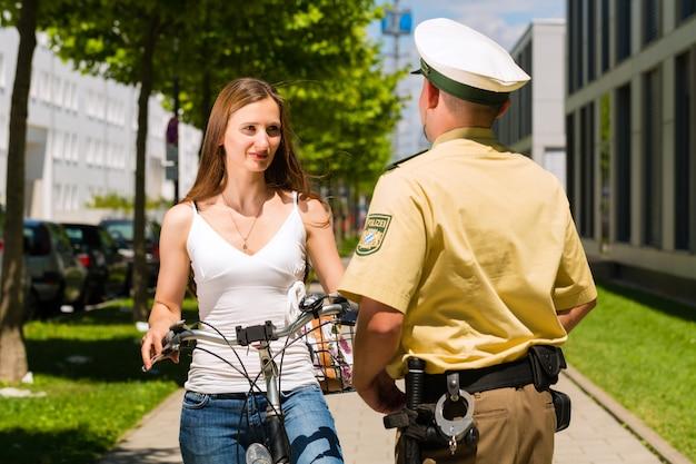 Polizia, donna in bicicletta con ufficiale di polizia Foto Premium