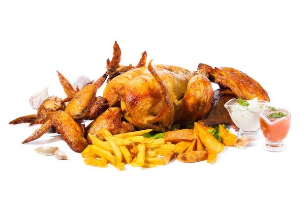 Pollo alla griglia, ali e cosce alla griglia con patatine fritte su sfondo bianco isolato Foto Premium