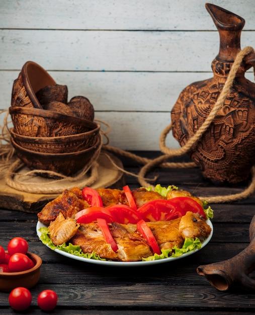 Pollo alla griglia guarnito con fettine di pomodoro su foglie di lattuga Foto Gratuite