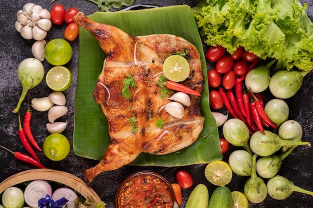 Pollo alla griglia su un piatto con peperoncino, salsa all'aglio e cosparso di semi di pepe. Foto Gratuite