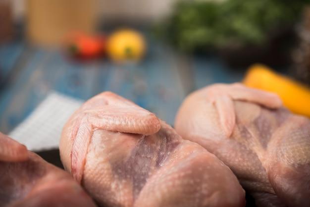 Pollo crudo del primo piano sul bordo di legno con gli ingredienti Foto Gratuite